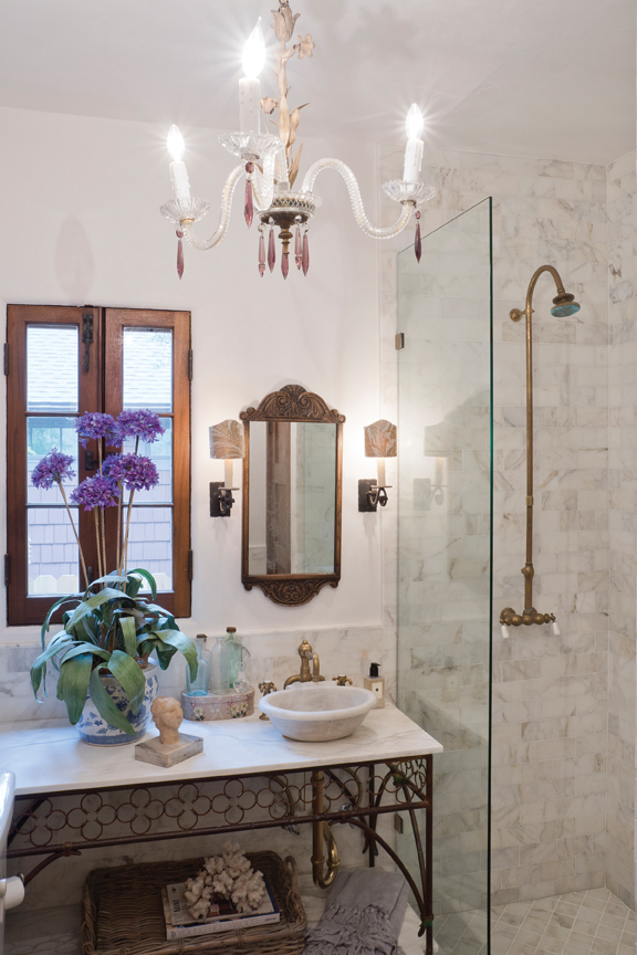 """Kate calls the guest bath the """"prison bathroom"""" because it is so tiny. When she remodeled, she refused to tear the room up. She repurposed the brass plumbing for the shower and added tile to the walls. The toilet is from the early 1930s, when toilets were much smaller than today. The vanity is a repurposed table with a sink cut into it."""