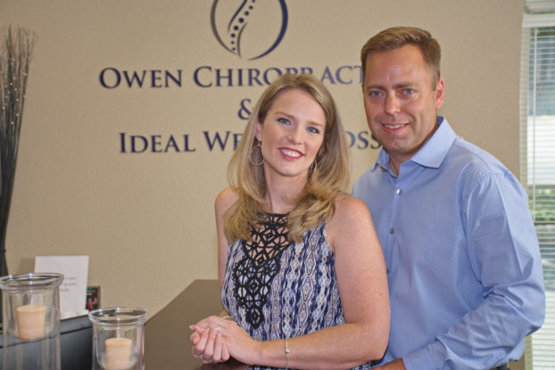Husband and wife owners of Owen Chiropractic and Ideal Weight Loss stand and smile in their front office.
