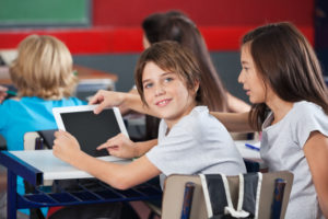 Young boy uses tablet with his peers in his classroom while smiling.