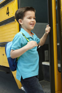 Young boy smiles while getting onto school bus.