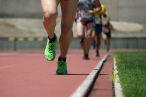 Close-up picture of four people's legs running single file on a track.