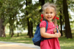 Small child with braids smiles while wearing a back-pack and going to school.
