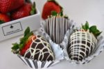 Picture of three chocolate covered strawberries with strawberries in the background.