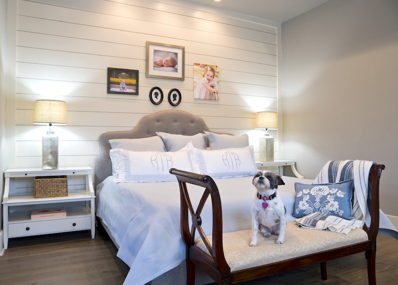 A shiplap wall in the master bedroom brings farmhouse tranquility to the private quarters where photography and children's silhouettes are displayed. Hand embroidered linens and bedding from Lin Marché. One of the three family dogs, Little Molly, holds court on a bench that once belonged to Katherine's mother.