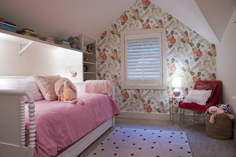 The bright, floral wallpaper was a favorite from her daughter's room in Stone Oak. Katherine loved the wallpaper and contacted designer Kim Wolfe to order the same paper for the new room. Built around the white barley twist day bed, custom shelves hold books, dolls and mementoes. Brass legged and rose velvet chair from Anthropologie.