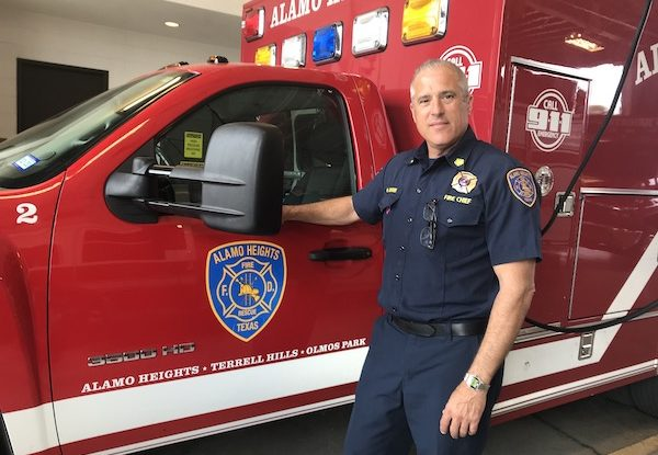 Alamo Heights Fire Chief Michael Gdovin standing in front of firetruck