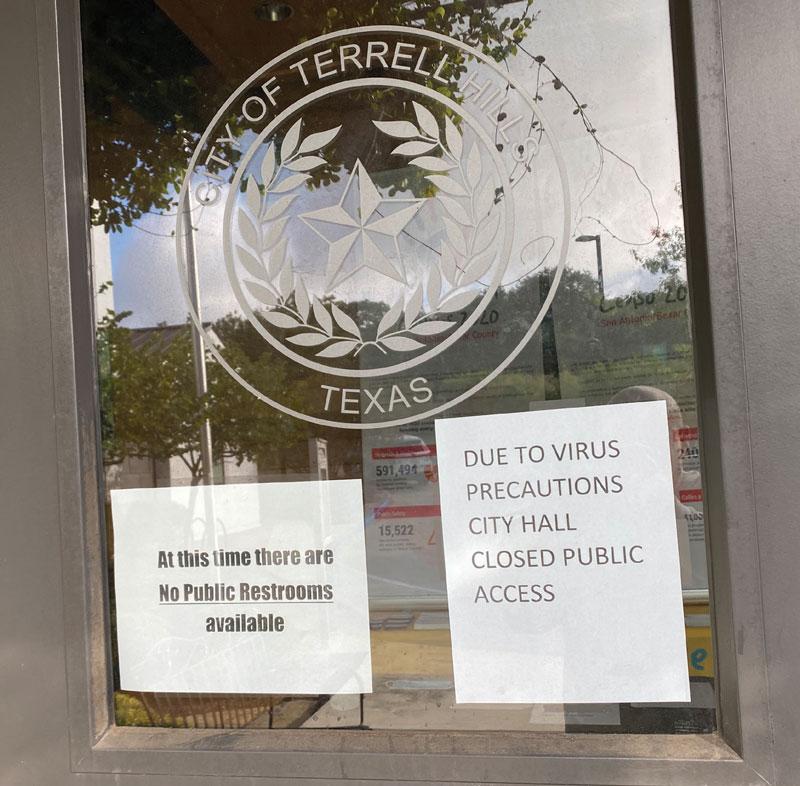 Terrell city hall door with COVID precaution signs