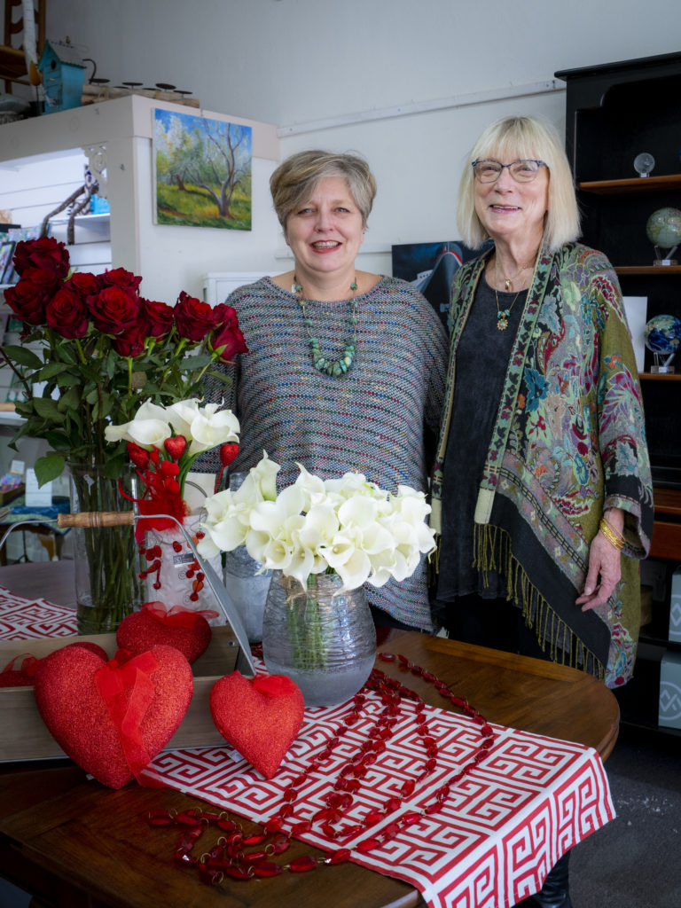 Two women smiling in a flower shop